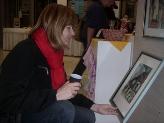 Věra Rosolová z Písku si prohlíží grafiku dětí z písecké DUHY. Nakonec jí neodolala.